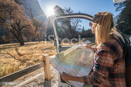 841604240 istock photo Road trip concept; Young woman sitting on car's hood looking at road map for directions exploring national parks and nature ready for adventure. 1161995412