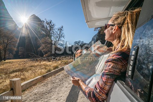 841604240 istock photo Road trip concept; Young woman sitting on car's hood looking at road map for directions exploring national parks and nature ready for adventure. 1161995539