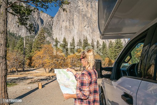 841604240 istock photo Road trip concept; Young woman sitting on car's hood looking at road map for directions exploring national parks and nature ready for adventure. 1161995599