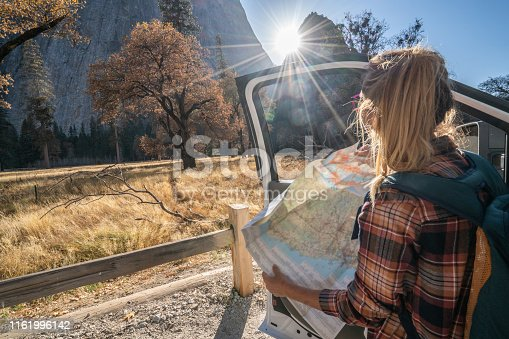 841604240 istock photo Road trip concept; Young woman sitting on car's hood looking at road map for directions exploring national parks and nature ready for adventure. 1161996142