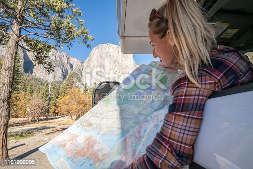 841604240 istock photo Road trip concept; Young woman sitting on car's hood looking at road map for directions exploring national parks and nature ready for adventure. 1161996295