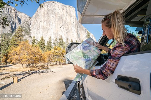 841604240 istock photo Road trip concept; Young woman sitting on car's hood looking at road map for directions exploring national parks and nature ready for adventure. 1161996486