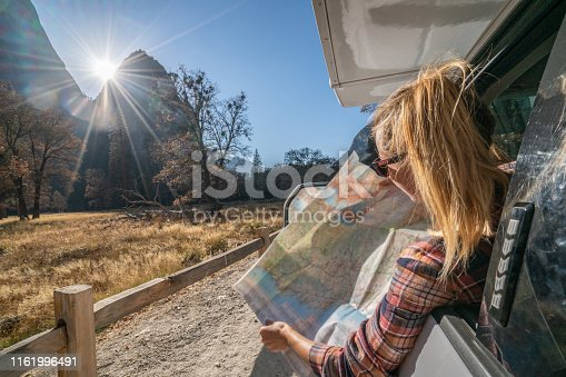 841604240 istock photo Road trip concept; Young woman sitting on car's hood looking at road map for directions exploring national parks and nature ready for adventure. 1161996491