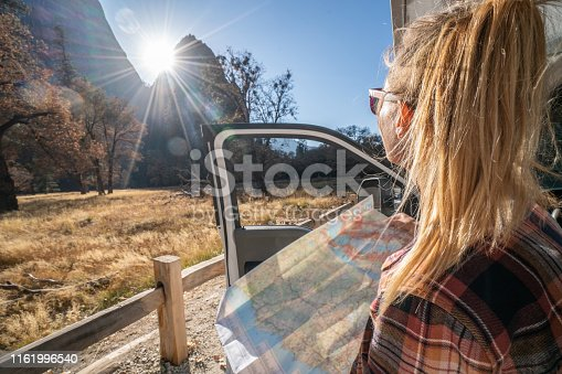 841604240 istock photo Road trip concept; Young woman sitting on car's hood looking at road map for directions exploring national parks and nature ready for adventure. 1161996540