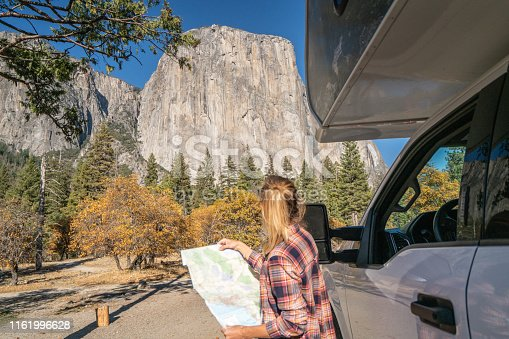 841604240 istock photo Road trip concept; Young woman sitting on car's hood looking at road map for directions exploring national parks and nature ready for adventure. 1161996628