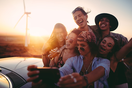 Group of friends taking selfies with a smartphone outdoor at sunset