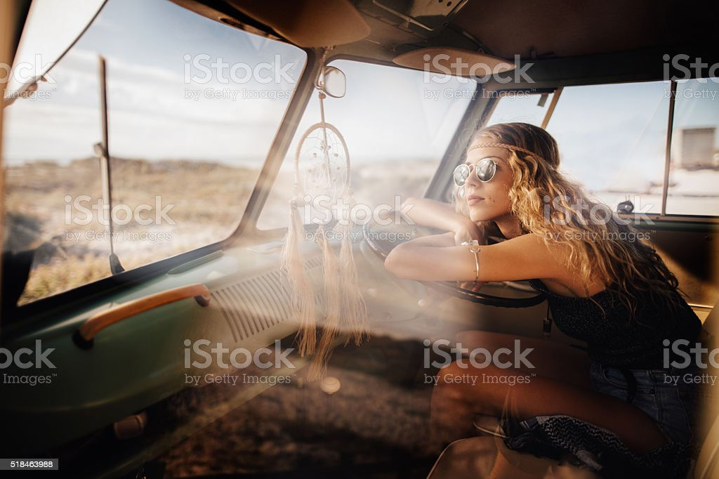 Road Trip Hipster Girl Sitting in Retro Van at beach stock photo