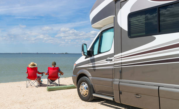 road trip in usa, couple relaxing near water - motorhome stock photos and pictures
