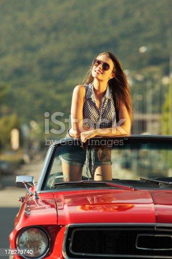 Beautiful young woman in a convertible car enjoying a summer day