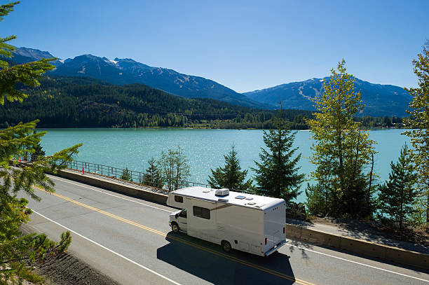 RV Road Trip RV driving along a spectacular section of Highway 99 past Green Lake in Whistler, BC motor home stock pictures, royalty-free photos & images