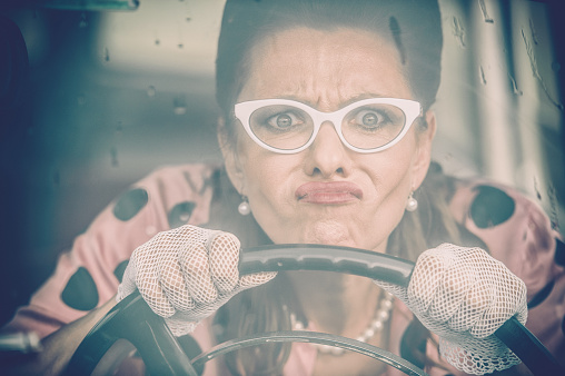 Mature woman who wearing white retro styled glasses, lace gloves, pearl necklace and doted blouse driving an oldtimer car in the rain - 1950 style. Purple toned image image.