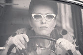 Mature woman who wearing white retro styled glasses, lace gloves, pearl necklace and doted blouse driving an oldtimer car in the rain - 1950 style. Black and white image.