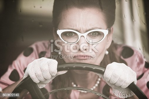 Mature woman who wearing white retro styled glasses, lace gloves, pearl necklace and doted blouse driving an oldtimer car in the rain - 1950 style. Horizontal sepia toned image.