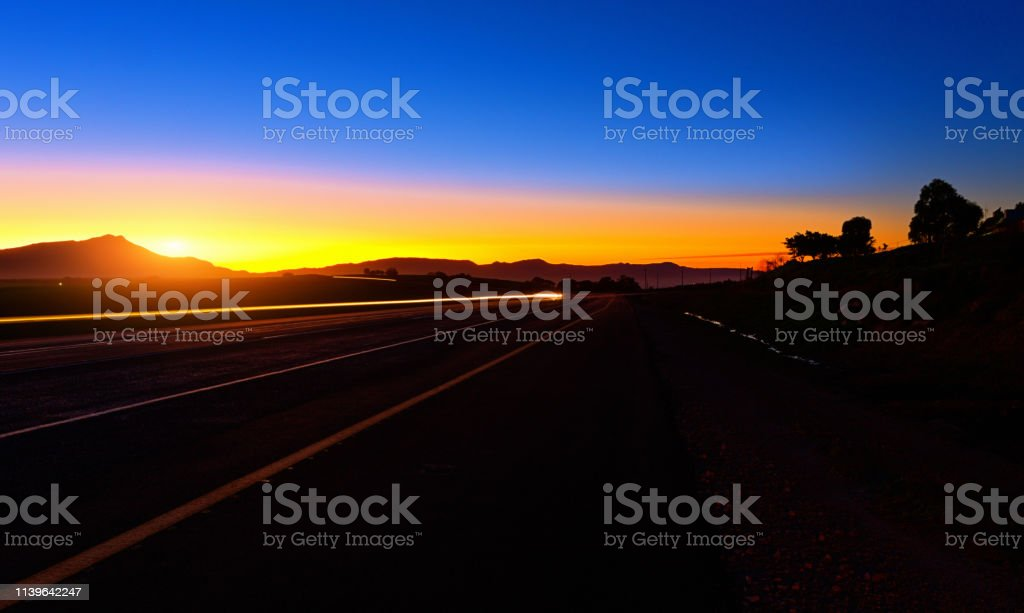 Seen while driving a long and empty road, the sun either rises or...