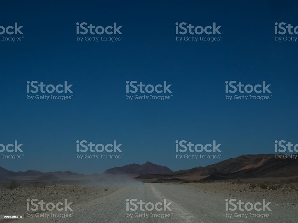 Road trip through dusty unpaved road among desert and mountain landscape foto stock royalty-free