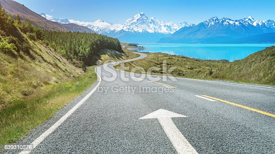Panorama of the road to Mount Cook along the turquoise Lake Pukaki with an forward pointing arrow country road marking. South Island, Canterbury, Mount Cook, Lake Pukaki, New Zealand