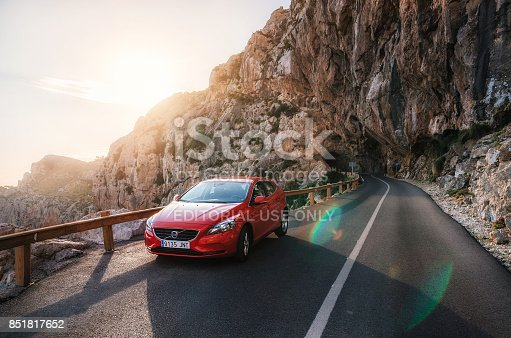 Alcudia, Mallorca, Spain - May 24, 2016: Red car Volvo V40 traveling on the mountain serpentine through a tunnel of a rock along the coast of Majorca against the sunshine. Roadtrip around Spain