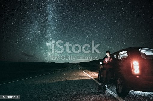 Driver takes a break on a lonely road under the milky way.