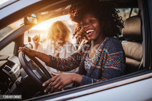 Two young cheerful female friends having fun on road trip in car at sunset