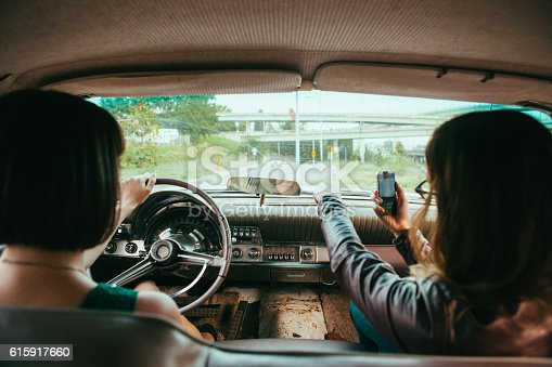 Lifestyle stock image of two young woman driving vintage american car. The passenger uses smart phone to pull up directions on the GPS app.
