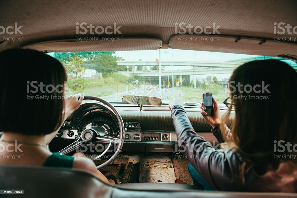 Road Trip Women in Vintage American Car and Phone GPS stock photo