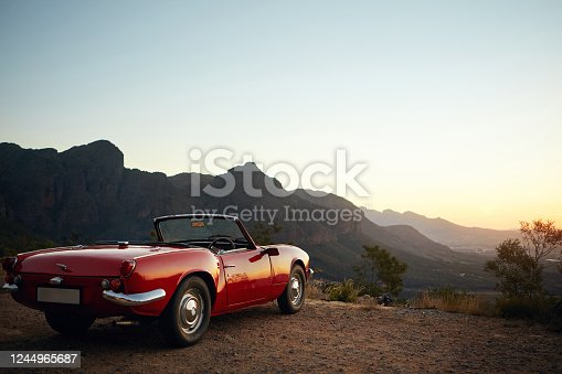 Shot of a vintage car parked on the side of a mountain