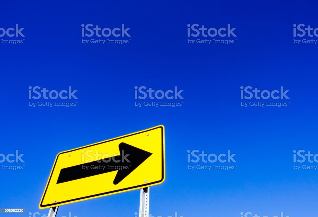 US road type one-way sign seen against a clear blue sky in late summer. stock photo