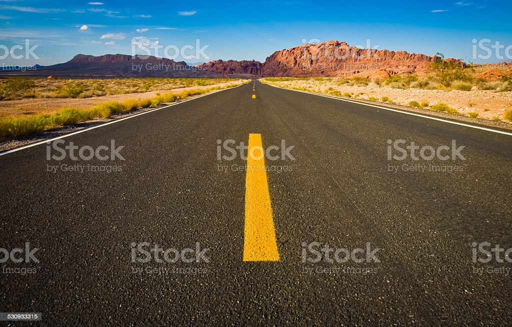 Road view towards mountains in desert stock photo
