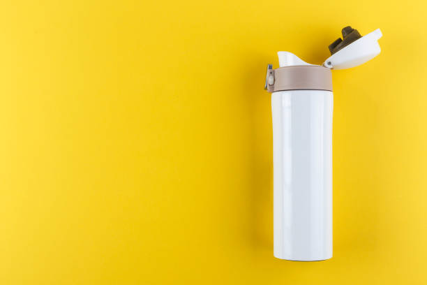 road white thermos with an open lid on a bright yellow background. stock photo