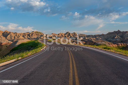 Road Winds Through Badlands Rock Formations on Early Summer Morning