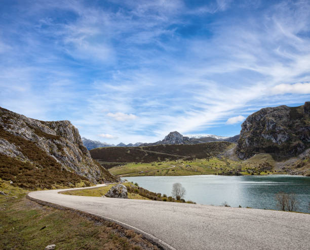 A road with a beautiful view near Lake Enol at sunny day , Picos de Europa Western Massif, Cantabrian Mountains, Asturias, Spain. stock photo