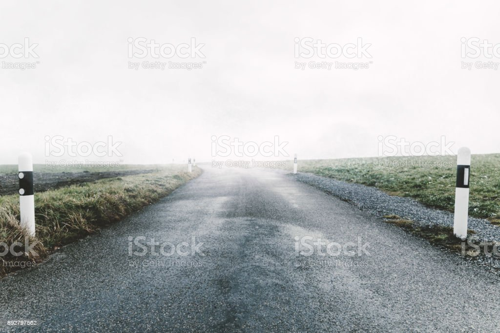 road with delineators in the morning fog stock photo