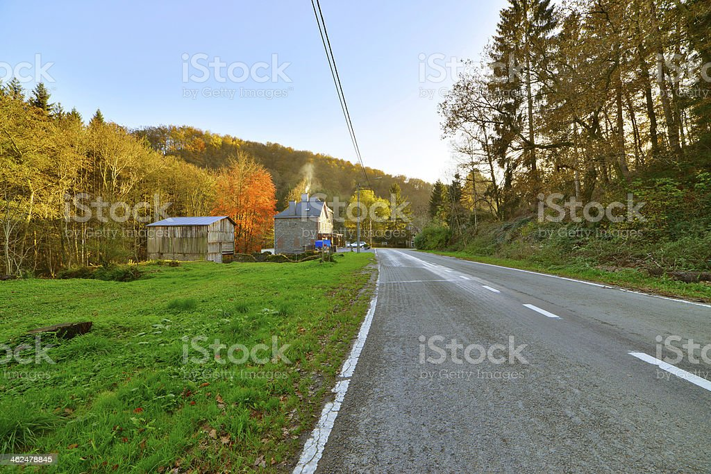 Road with houses and trees in autumn mountain landscape. stock photo