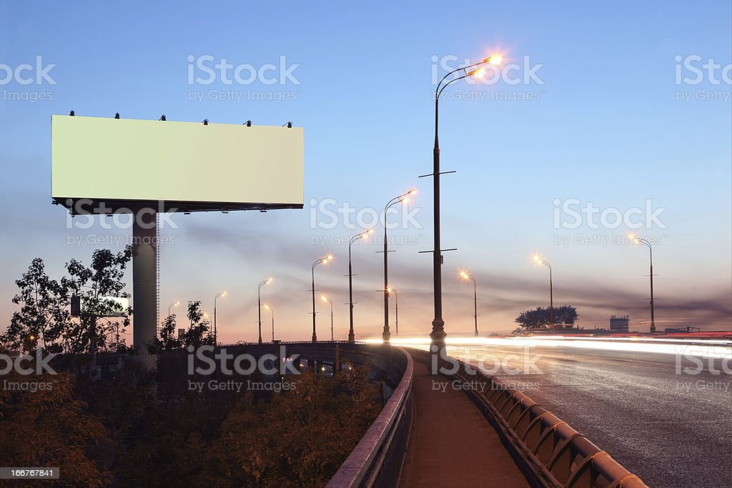 Road with large blank billboard at evening royalty-free stock photo