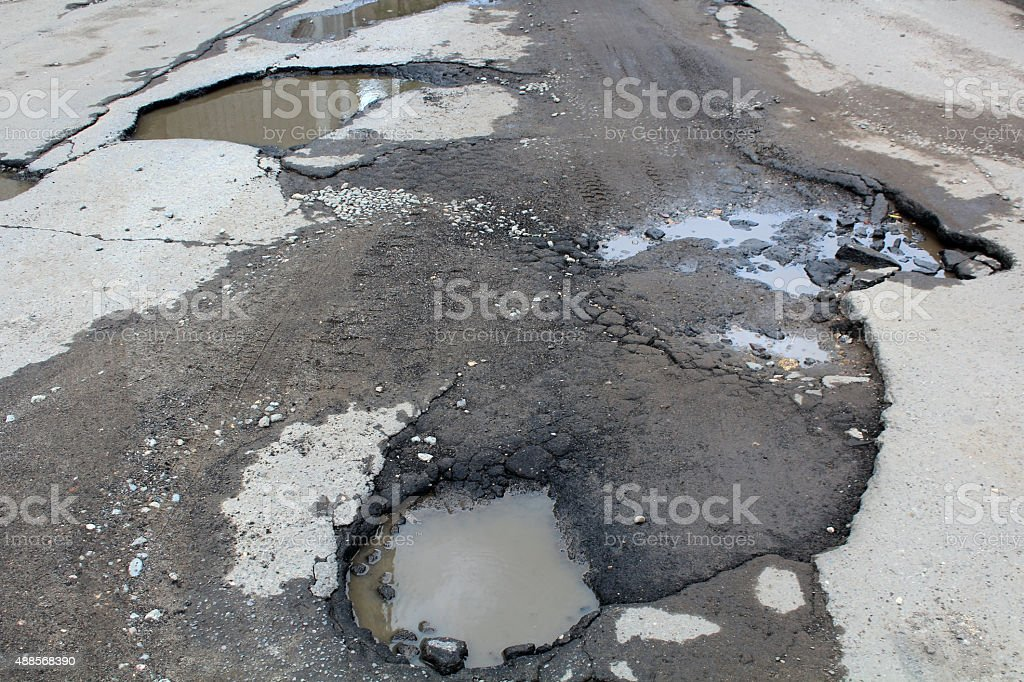road with potholes and puddles stock photo