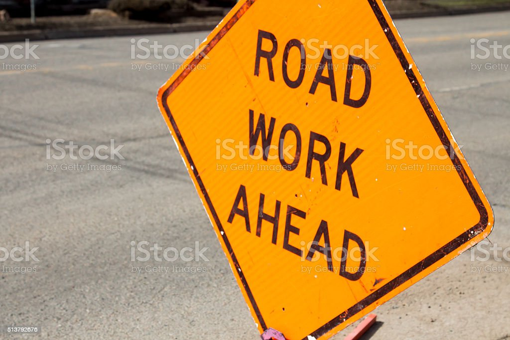 Road work ahead sign against asphalt road stock photo