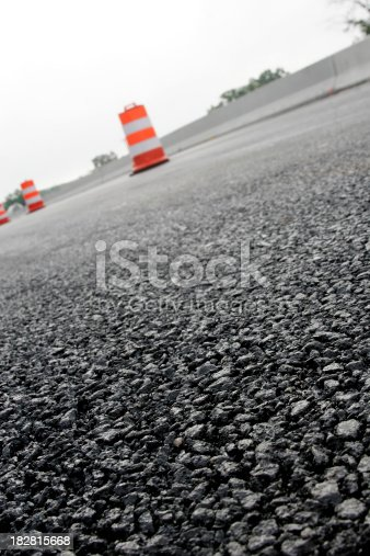 Road construction shot with shallow depth of field. Focus is on the asphalt in foreground.