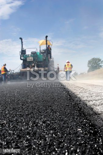A crew of men lay asphalt on a road. Focus is shallow and on the foreground.