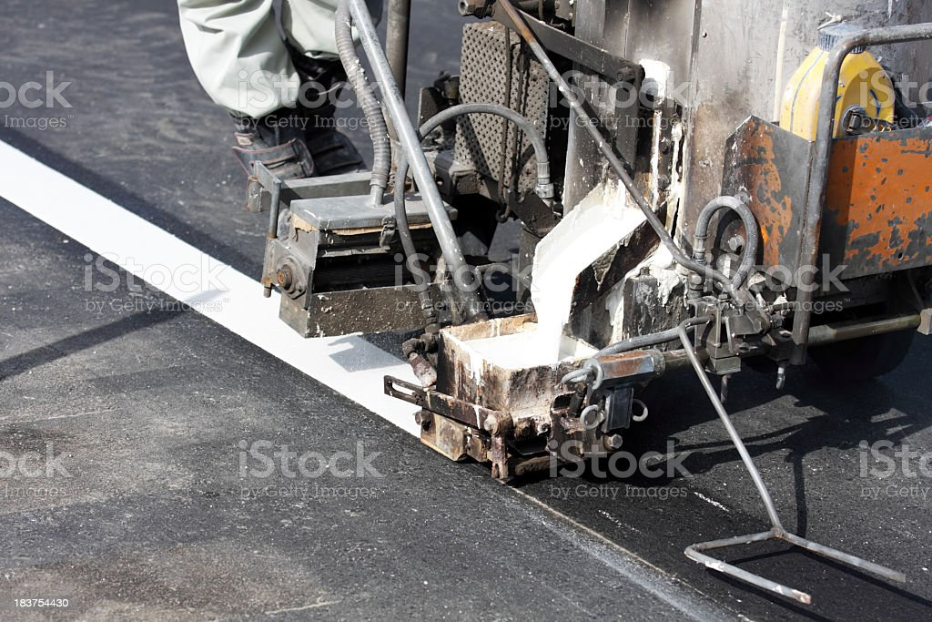 Road worker makes a line on new asphalt royalty-free stock photo