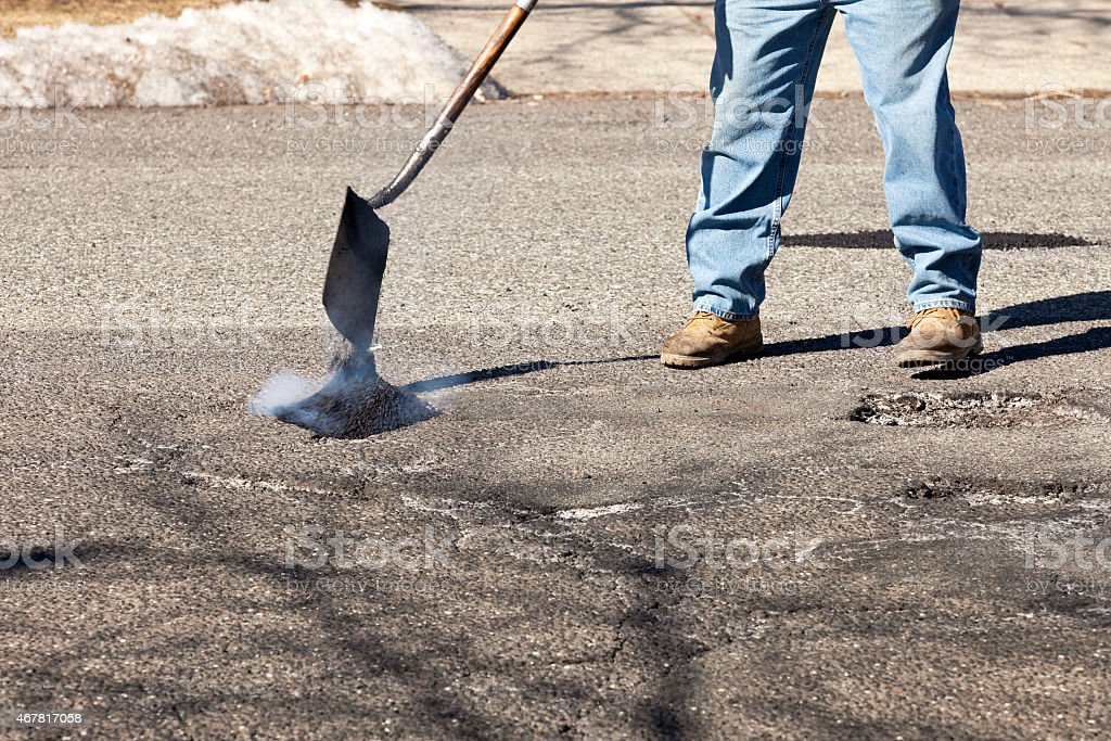 Road worker shoveling and dumping hot asphalt filling potholes stock photo
