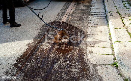 Road worker spraying bitumen emulsion with the hand spray lance before applying a new layer of asphalt