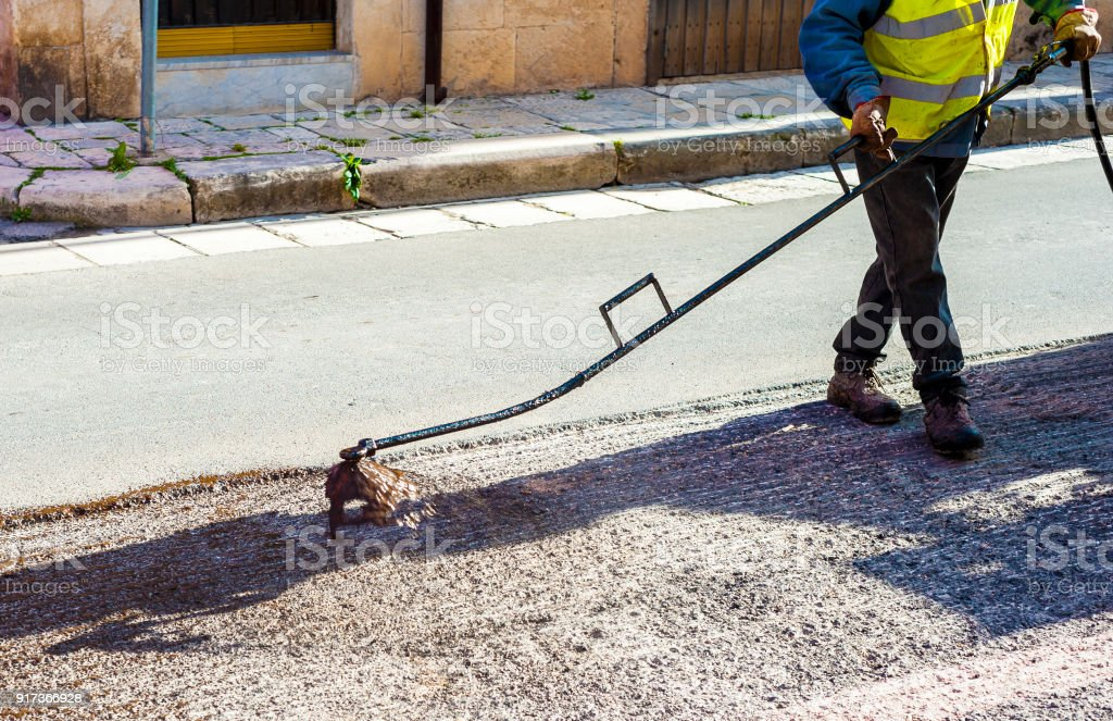 Road worker spraying bitumen emulsion with the hand spray lance before applying a new layer of asphalt stock photo