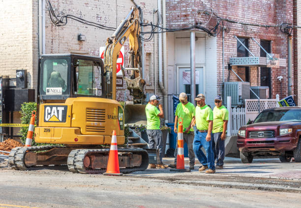 Road workers and Caterpillar tractor on city street. stock photo