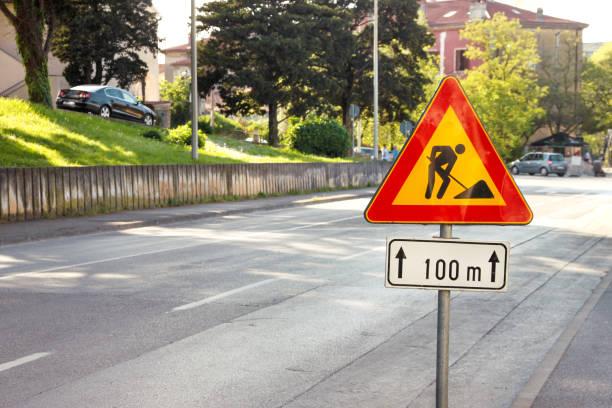 Sinal de obras rodoviárias para construção funciona na rua da cidade. Estrada sob o sinal de tráfego de construção. Tráfego, aviso a reparação da estrada de sinal. Sinal de rua ao ar livre. Vermelho, preto e amarelo triângulo estrada sinal de tra - foto de acervo