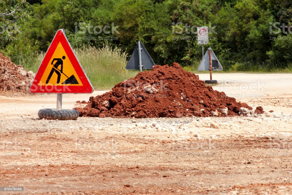 Road works sign for construction works, road, pavement construction. Traffic, warning sign road repairing, road maintenance. Red, black, yellow triangle road sign work. Reconstruction, infrastructure. stock photo