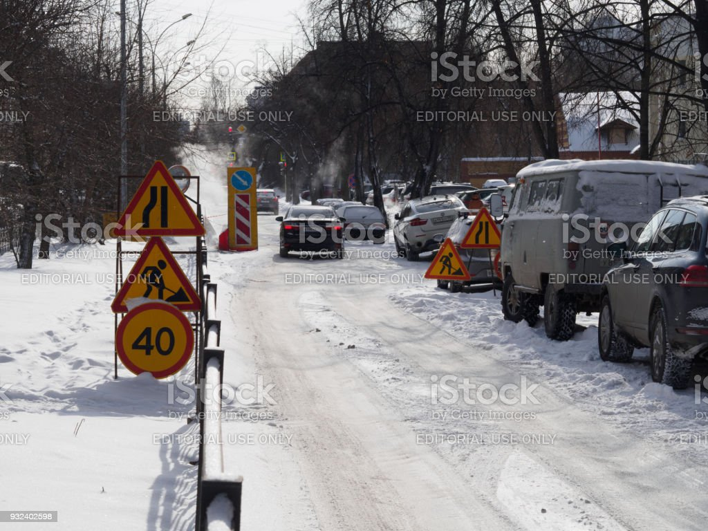 Road works signs and speed limit sign around hole stock photo