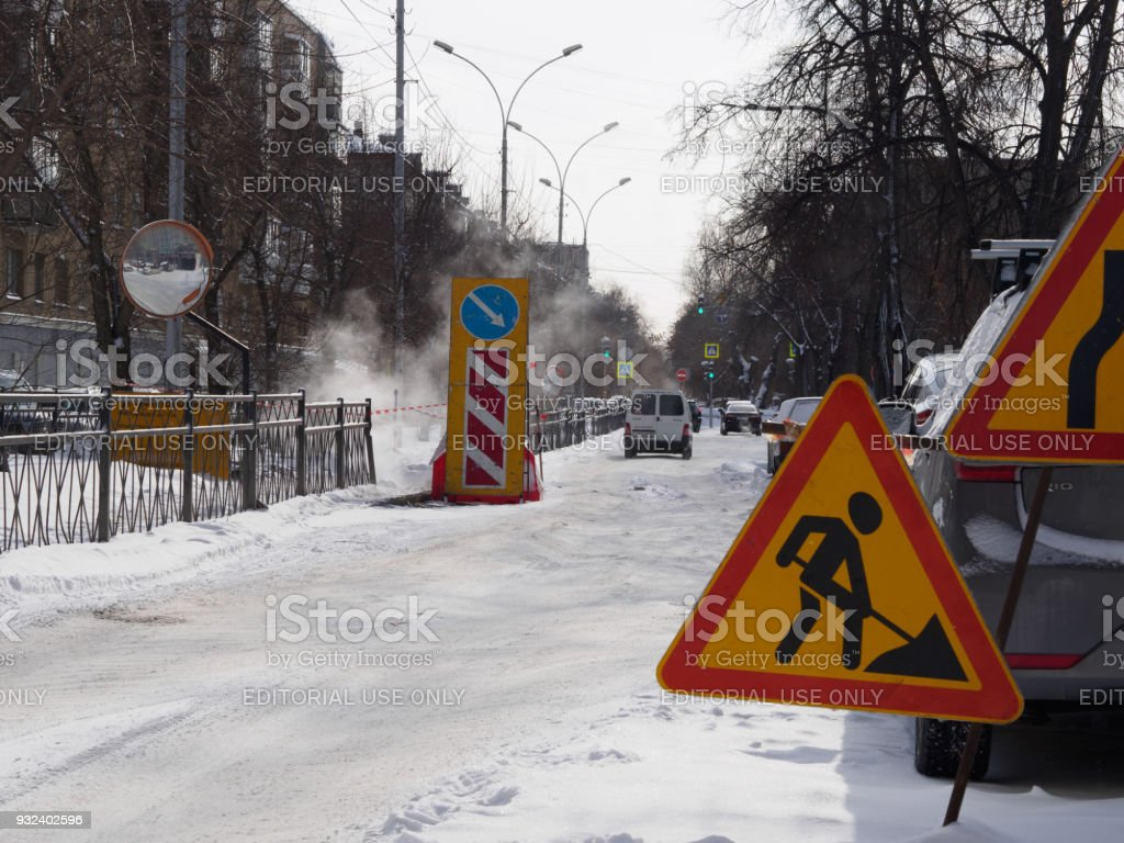 Road works signs around hole with steam stock photo