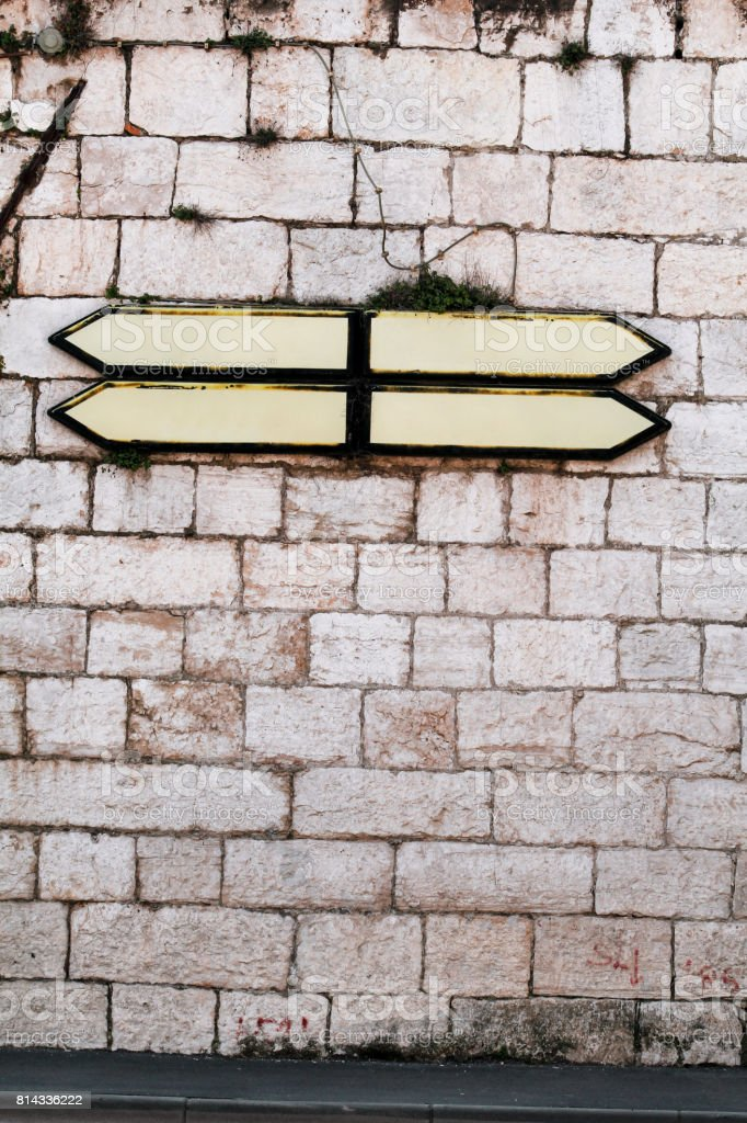 Roadmap signs and guidepost with a stone wall in background. Direction Signboard on the old stone wall. Background and Texture for text or image. stock photo
