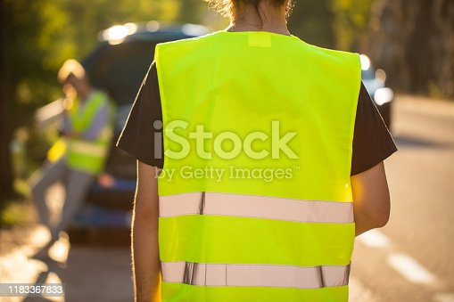 Rear view of auto mechanic coming to help young woman with her car problem, wearing fluorescent waistcoats