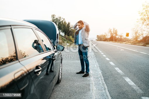Car issue breakdown or engine failure. Elegant middle age man waiting for towing service for help car accident on the road. Roadside assistance concept.